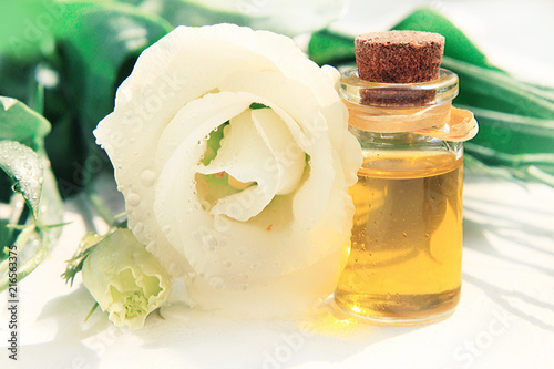 Glass bottle of golden aroma essential oil with delicate white glass bottle of golden aroma essential oil with delicate white flower blossom close up mightylinksfo