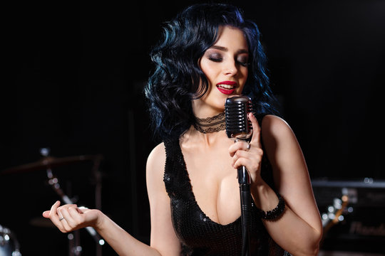Beautiful sensual woman with retro microphone singing songs on the stage