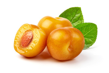 Juicy yellow plums and a half of yellow plum fruit with leaves, isolated on white background.