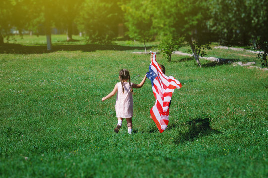 Children - a boy and a girl with an American developing flag in their hands running on a green lawn
