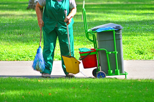 Cleaning service for park areas. Gardener with equipment and bucket on wheels.