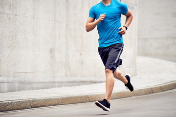Athletic man jogging on road in the city. Sport and fitness concept