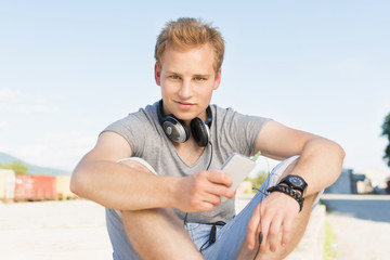Young millennial man with smartphone and headphones outdoors on sunny summer day. No retouch, closeup, natural lighting.