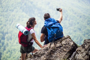 Couple of hikers using smartphone and make selfie outdoor