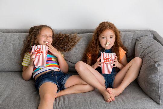 Young girls on grey sofa eating pop corn