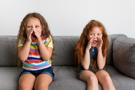 Little girls sitting on sofa screaming with hands around mouth