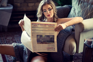 Female portrait of cute lady with newspaper indoors