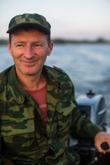 Portrait of a man in camouflage driving a motor boat.