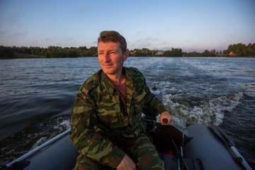 Hunter in camouflage drives a motor boat on the lake.