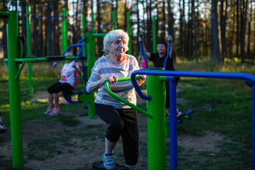 An elderly woman is doing exercises on the sport playground in the Park.