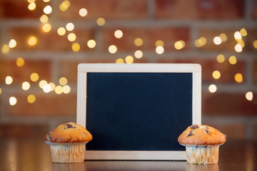Real homemade classic cupcakes and blackboard. Fairy lights and gift box in bokeh background. Christmas time concept
