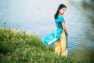 Beautiful young Asian girl outdoors, Ao dai - famous traditional costume for a woman in Vietnam