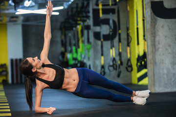 Happy lady is exercising obliques in static position in fitness studio. She is balancing on one elbow and raising other arm while looking at it. Athlete is training both strength and flexibility