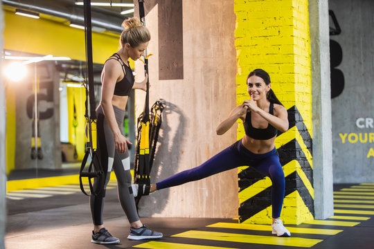 Positive lady is doing side lunges with trx straps in fitness studio. Woman instructor is supervising her performance. She is standing beside and holding rope