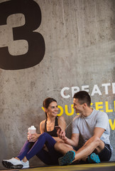 Cheerful couple is relaxing during break in workout in gym. They are sitting on floor and sharing earphones while enjoying audios. Man is holding smartphone while girl is drinking water from sport