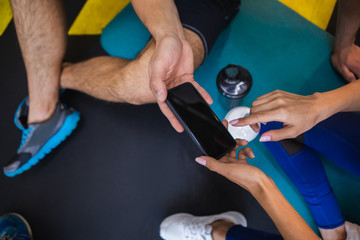 Top view close up of smartphone held both by male and female hands. Two sportspeople are sitting on mats in sport studio with bottles of water. Woman is pointing at screen for attracting man attention