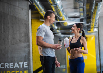 Grinning sporty couple is talking after training in gym. Man and woman are standing and looking at each other while holding water in hands
