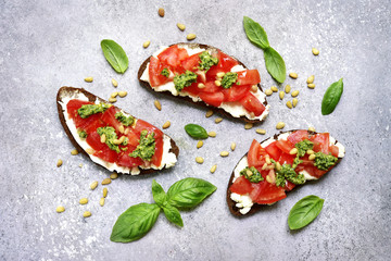 Photo sur Plexiglas Plat cuisine Rye toasts with soft cheese, tomatoes, pine nuts and pesto sauce. Top view with copy space.