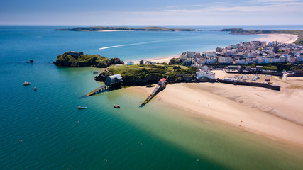 Aerial drone view of a beautiful coast town with sandy beaches and colorful buildings (Tenby, Wales, UK)