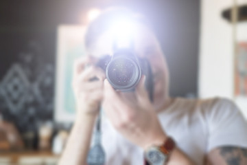 A man takes pictures on a camera with a flash