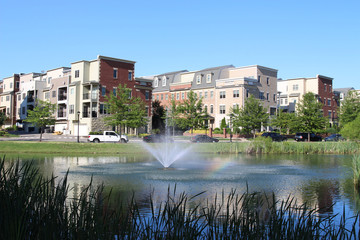 A pond with a fountain at modern townhouses in the summer. Richmond suburbs, Virginia