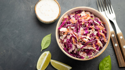 Purple cabbage and carrot salad with mayonnaise in a white bowl on a black background. Classic coleslaw. Diet vegetarian dish. Top view with copy space