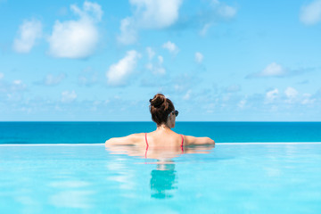 Woman relaxing on vacation in infinity edge swimming pool