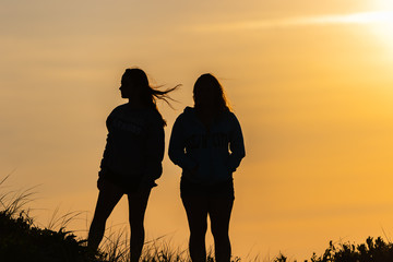 Two women silhouetted  by the setting sun on a sand dune in Assateague Island.