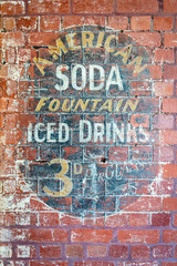 A weathered and faded American Soda Fountain sign found on the side of an Australian office building