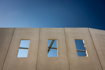 Prefabricated concrete walls with windows, being erected against a blue sky with support structures visible