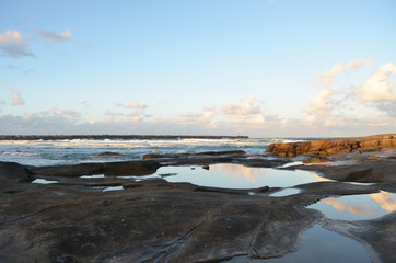 The colours of sunset are reflected in the still water of some rock pools. The sky is blue, with some clouds on the horizon.