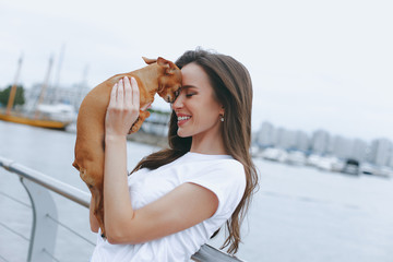 Young attractive woman is walking with dog on sea promenade