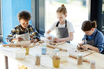 Three children in aprons sitting by table, kneading clay and making earthenware at lesson