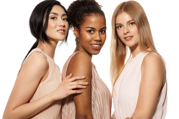 Portrait of three cute young smiling girls of different nationalities posing at studio in nude dresses. Happy lovely models looking at camera with gladness. Isolated on white background