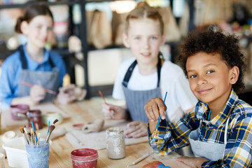 Happy mixed-race boy with paintbrush looking at you at lesson of art and craft
