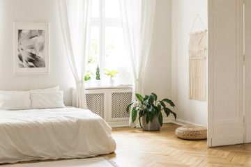 Beige macrame and a poster on the white walls of a bright, minimalist bedroom interior with herringbone hardwood floor and plants