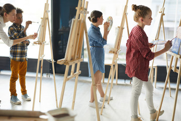 Two schoolgirls and schoolboy standing by their easels and painting while teacher consulting one of them