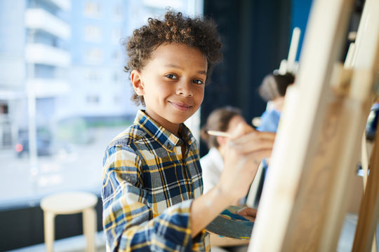 Happy mixed-race pupil looking at camera while standing by easel and painting at lesson in studio of arts