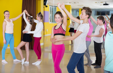Teenagers in pairs learning to dance active boogie-woogie