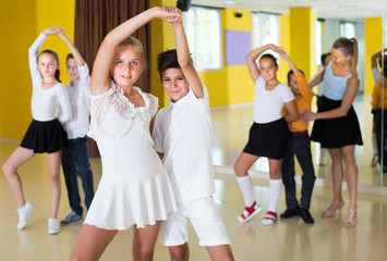Positive kids are dancing twist in pairs