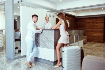 couple near reception desk in hotel