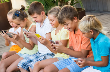 Group of friendly kids playing with mobile phones outdoors