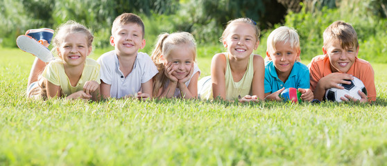 Group of friendly kids lying on green grass in park