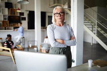 Mature blonde businesswoman in casualwear crossing arms on chest while standing by her workplace