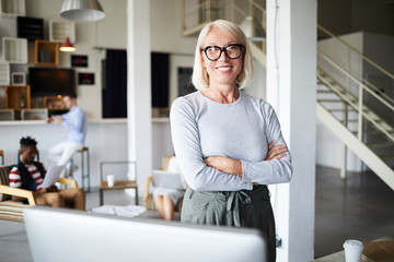 Smiling blond woman with crossed arms looking at you by her workplace