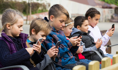 Outdoor portrait of girls and boys playing with phones