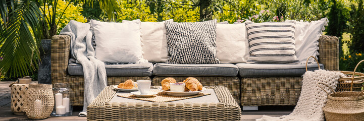 Cushions on settee and rattan table on patio in the garden during summer. Real photo