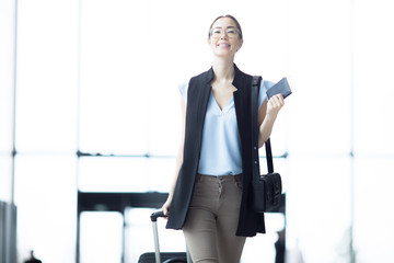 Cheerful and successful businesswoman with luggage moving inside modern airport after arrival