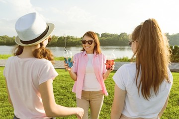 The happy mother is actively resting on nature with her teenage daughters 14 and 16 years old. Communication of parents and teenagers, Woman with summer drinks.