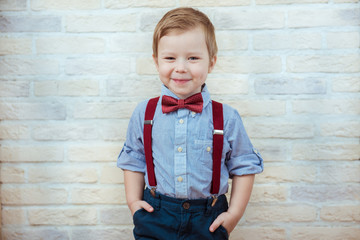Smiling child boy in fashionable clothes on brick wall background